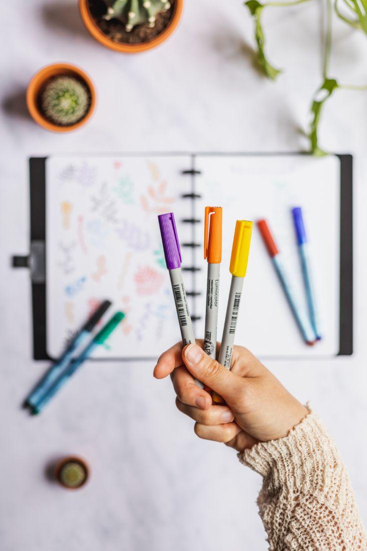 Arm hält einen lila orange und gelb löschbaren Stift mit einem löschbaren Notizbuch, Stifte und Pflanzen im Hintergrund verschwommen