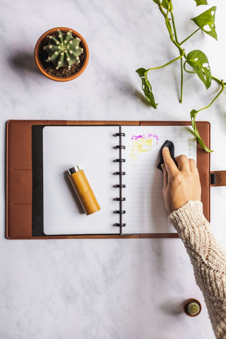 Löschen von Text in löschbarem Notizbuch mit braunem veganem Lederbezug auf Marmorhintergrund