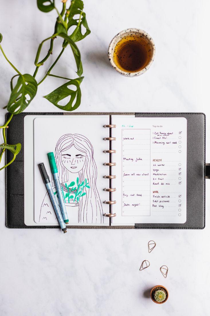 Löschbares Notizbuch mit Zeichnung und Aufgabenliste mit einem schwarzen und grünen Stift auf Marmorhintergrund