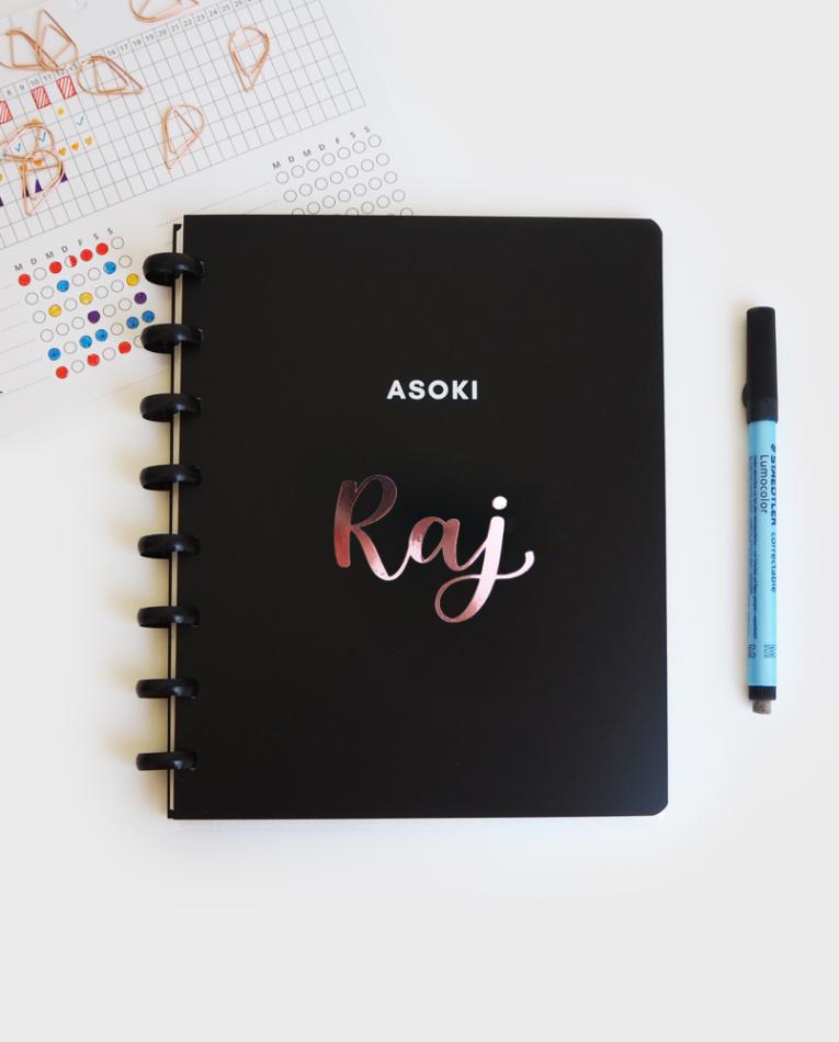 Wiederverwendbares Notizbuch mit schwarzem Cover und Ringbindung, als persönliches Merkmal kannst du dir deinen Namenssticker gestalten