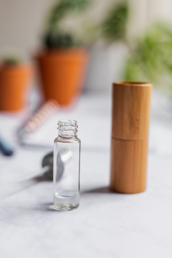 Kleine leere Sprühflasche ohne Verschluss neben Bambushalter mit im Hintergrund Verschluss und Pflanzen